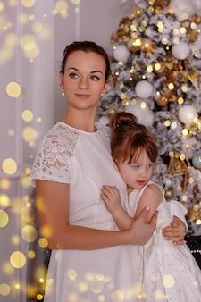 Mutter und tochter umarmen sich sanft vor dem hintergrund eines geschmückten weihnachtsbaums