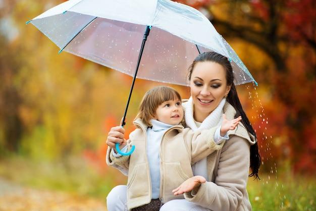 Mutter und tochter unter dem regenschirm verstecken sich vor dem regen. glückliche lustige familie mit rotem regenschirm unter der herbstdusche. mädchen und ihre mutter genießen regen. im park spazieren gehen.