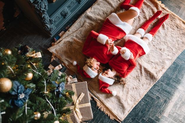 Mutter und tochter warten auf neujahrsgeschenke in der nähe des weihnachtsbaumes.