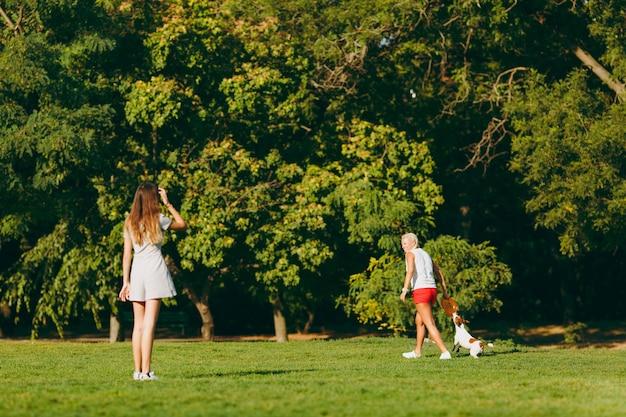 Mutter und tochter werfen einem kleinen lustigen hund eine orangefarbene flugscheibe, die ihn auf grünem gras fängt. kleines jack russel terrier haustier, das draußen im park spielt. hund und frauen. familie ruht sich im freien aus