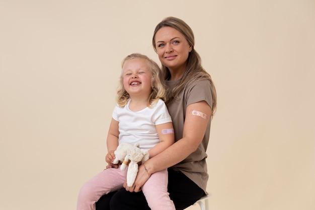 Mutter und tochter zeigen aufkleber am arm, nachdem sie einen impfstoff bekommen haben