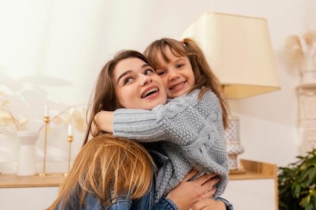Mutter und tochter zu hause umarmen sich