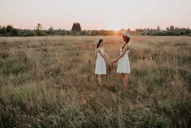 Mutter und tochter zusammen in den weißen kleidern mit borten und blumenkränzen in boho-art auf dem sommergebiet bei sonnenuntergang