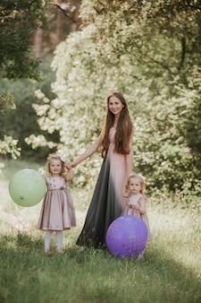 Mutter und tochter zwei, die spaß im park haben. happy family-konzept. schönheitsnaturszene mit lebensstil der familie im freien. glückliche familie, die zusammen stillsteht. glück und harmonie im familienleben.