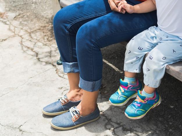 Mutter- und tochterbeine, die auf dem stuhl im park sitzen. glückliches familienkonzept.