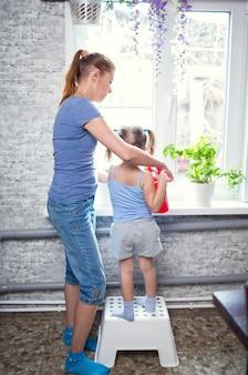 Mutter- und tochterfamilie, die zu hause blumen am fenster gießt