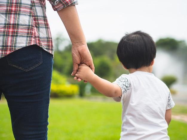 Mutter- und tochterhändchenhalten, die in den park gehen. kind und mutter familienkonzept.