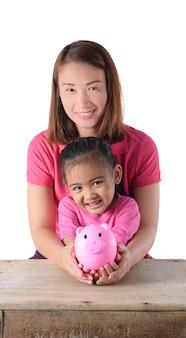 Mutter- und tochterhand, die sparschwein lokalisiert auf weißem hintergrund hält