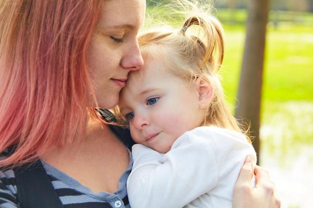 Mutter- und tochterportrait umarmen das küssen im park