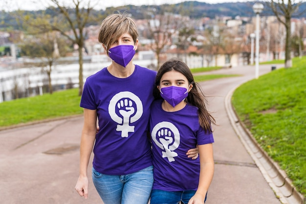 Mutter und töchter gehen die straße entlang und tragen ein lila t-shirt mit dem symbol der berufstätigen frau am internationalen frauentag, dem 8. märz, und eine maske für die coronavirus-pandemie