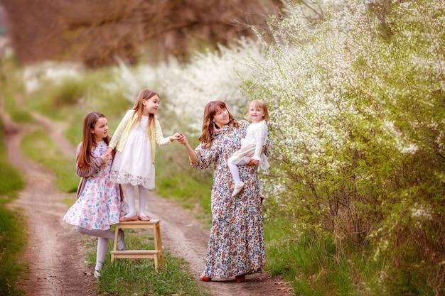Mutter und töchter in der nähe eines blühenden busch-, frühlings-, frühlingsfamilienfoto-shootings