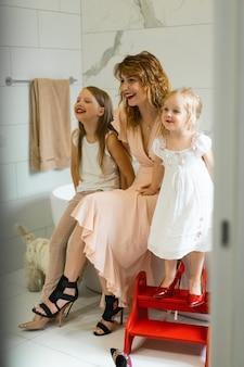 Mutter und töchter schminken im bad, tragen lippenstift vor dem spiegel auf.
