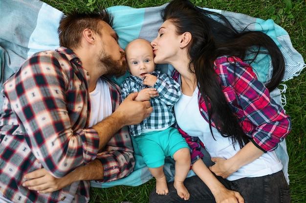 Mutter und vater küssen ihr kleines baby, draufsicht