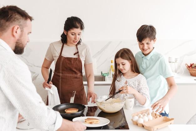 Mutter und vater mit zwei kindern 8-10 kochen zusammen und braten pfannkuchen auf modernem herd in der küche zu hause