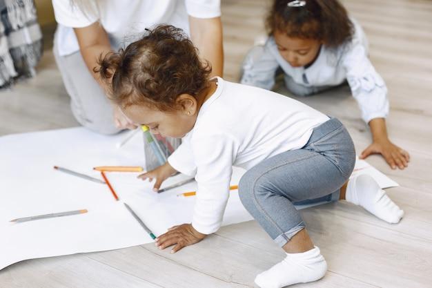 Mutter und zwei afroamerikanische töchter, die zusammen zeichnen. erwachsene frau verbringt zeit mit ihren kleinen mädchen.