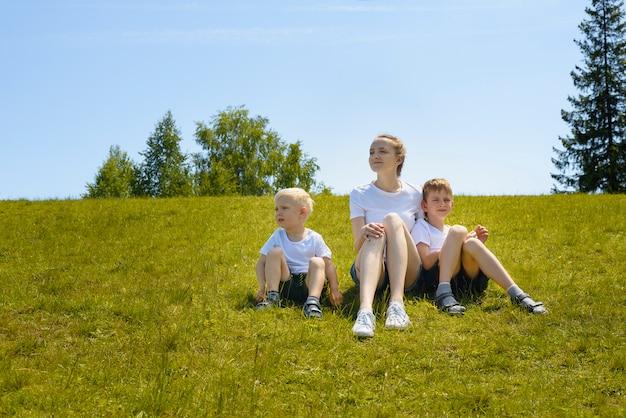 Mutter und zwei junge söhne sitzen auf gras
