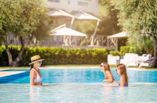 Mutter und zwei kinder genießen sommerferien im luxusschwimmbad
