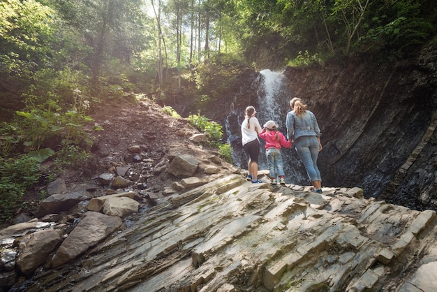Mutter und zwei kleine töchter von hinten stehen auf dem berg und genießen den bezaubernden blick auf den wasserfall, während sie an einem sonnigen sommertag durch die berge wandern