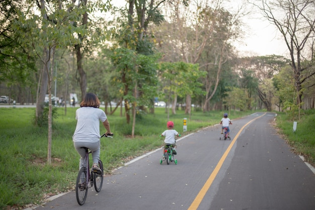 Mutter und zwei sohn fahren fahrrad auf fahrradweg.