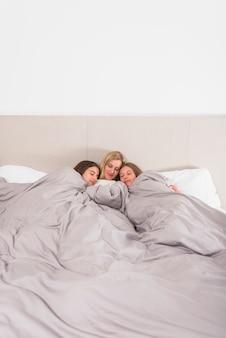 Mutter und zwei töchter, die im bett schlafen