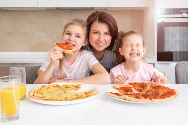 Mutter und zwei töchter essen hausgemachte pizza an einem tisch in der küche, glückliches familienkonzept