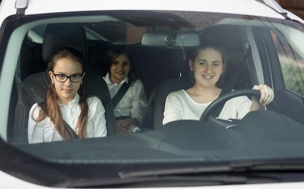 Mutter und zwei töchter in schuluniform fahren im auto