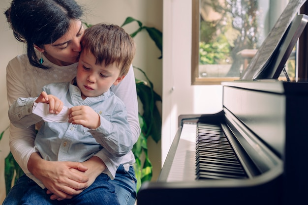 Mutter unterrichtet ihren sohn zu hause klavierunterricht. familienlebensstil, der zeit zusammen drinnen verbringt. kinder mit musikalischer tugend und künstlerischer neugier. musikalische bildungsaktivitäten für kleine kinder.