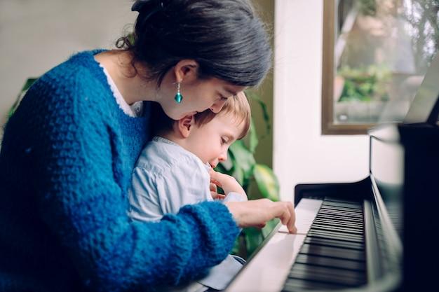 Mutter unterrichtet ihren sohn zu hause klavierunterricht. familienlebensstil, der zeit zusammen drinnen verbringt. kinder mit musikalischer tugend und künstlerischer neugier.