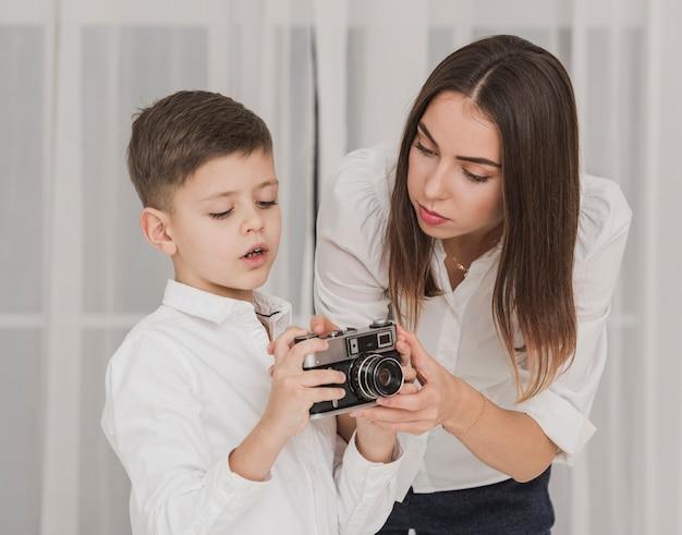 Mutter unterrichtet jungen, kamera zu benutzen
