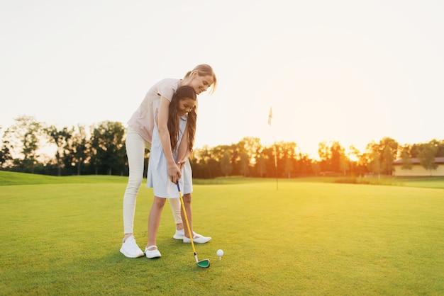 Mutter unterrichtet kind, schuss-golf spielendes familien-hobby zu nehmen.