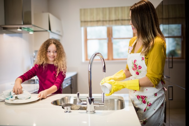 Mutter unterstützung tochter in waschplatte in der küche