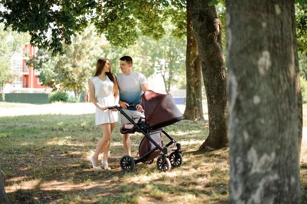 Mutter, vater und ihre kleine tochter im kinderwagen