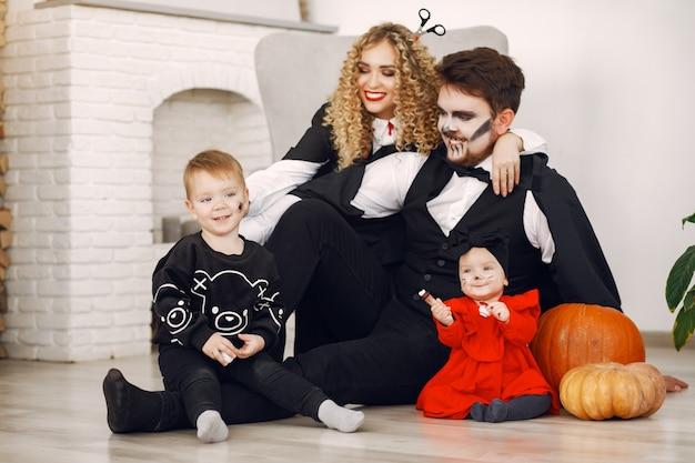 Mutter vater und kinder in kostümen und make-up. familie bereiten sich auf die feier von halloween vor.