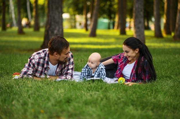 Mutter, vater und kleines baby entspannen auf gras im sommerpark