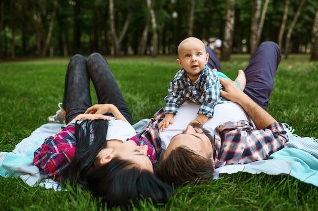 Mutter, vater und kleines baby entspannen sich auf gras