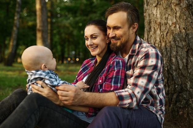 Mutter, vater und kleines baby sitzen unter dem baum im sommerpark
