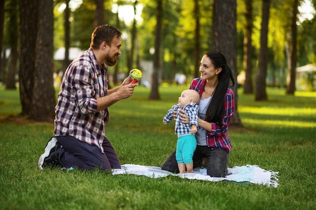 Mutter, vater und kleines baby spielen auf gras im sommerpark
