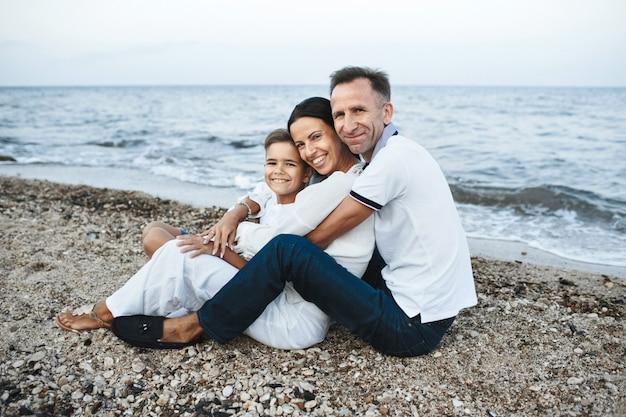 Mutter, vater und sohn sitzen am strand in der nähe des meeres, umarmen sich und schauen gerade