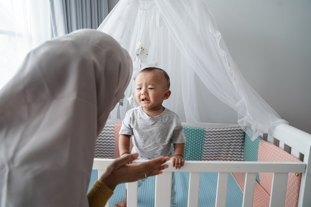 Mutter versucht, ihr weinendes kind an der krippe zu trösten