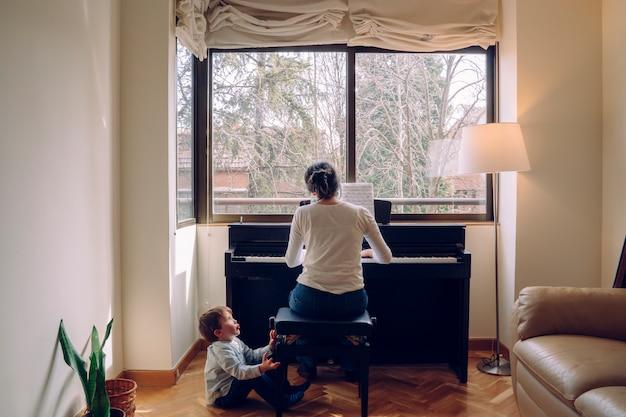 Mutter versucht zu hause klavier zu spielen, während sie sich um ungezogene kinder kümmert, als sie spielen will. Premium Fotos