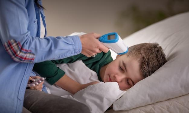 Mutter verwendet thermometer, um die temperatur ihres schlafenden jungen im bett zu messen.
