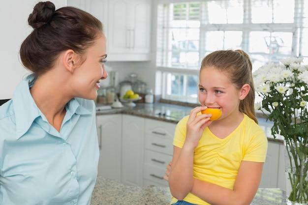 Mutter, welche die tochter isst orange in der küche betrachtet