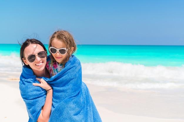 Mutter wickelt eine kleine tochter mit einem tuch ein, nachdem sie im meer geschwommen ist, mutter und kleine tochter, die zeit am tropischen strand genießen