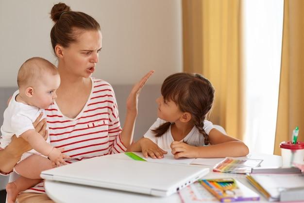 Mutter wird frustriert von der tochter, während sie hausaufgaben macht, die zu hause am tisch sitzen, bei lernschwierigkeiten, hausaufgaben, elternschaft und online-bildung.