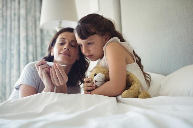 Mutter zeigt ihrer tochter die temperatur auf dem thermometer