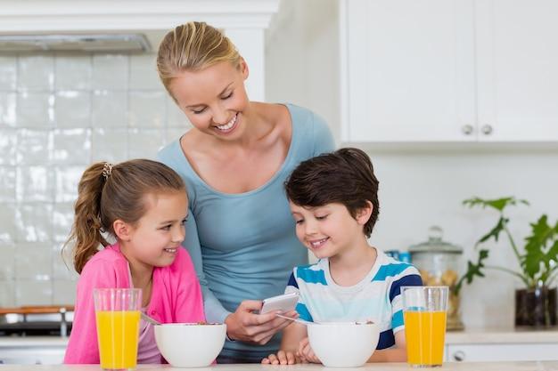 Mutter zeigt kindern beim frühstück das handy