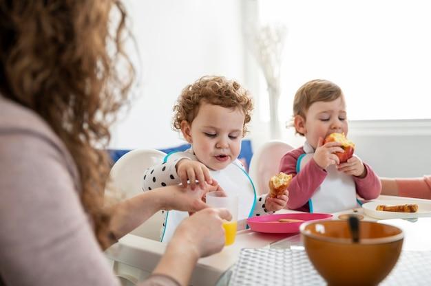 Mutter zu hause mit kindern beim mittagessen