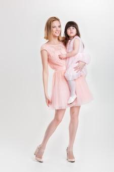 Mutterblondine, die eine niedliche kleine tochter in einem rosa prinzessinkleid auf einem grauen hintergrund hält. familie