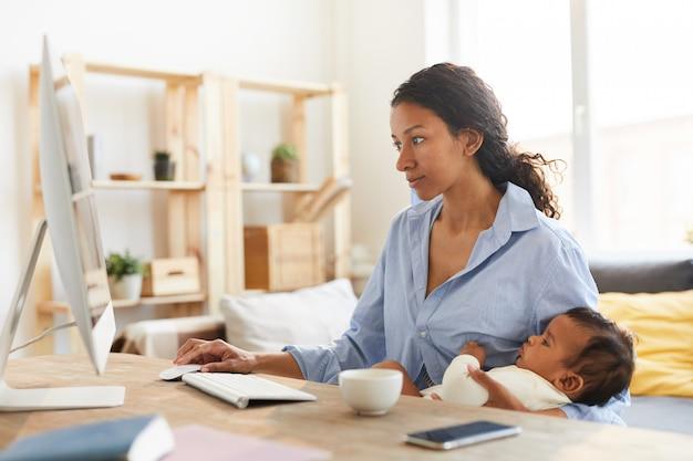Mutterdesigner, der an projekt arbeitet, während baby stillt