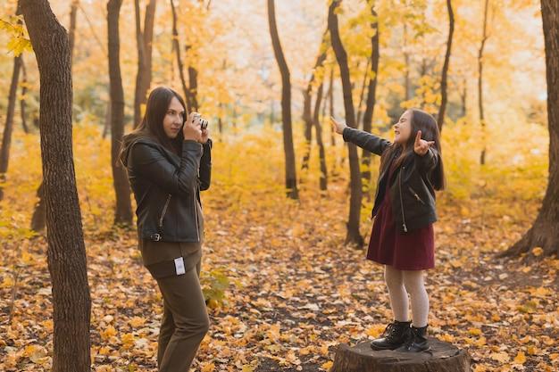 Mutterfotografin fotografiert ihre tochter im park im herbst, hobbys fotokunst und
